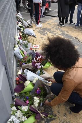Una mujer deposita un ramo de flores frente al resturante camboyano de la Rue Albert en París.