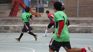 Unos jóvenes juegan a fútbol sala.