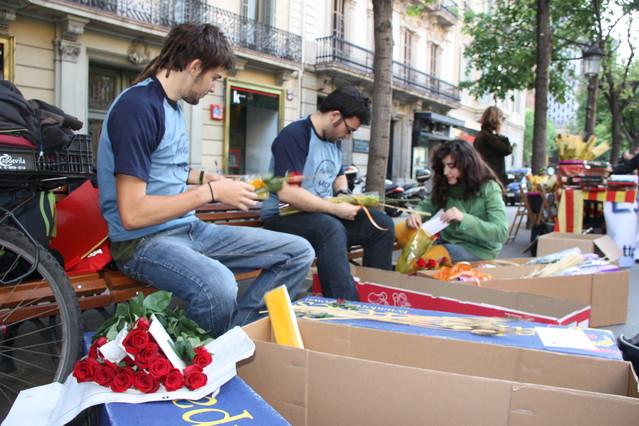 Unos jóvenes preparan su puesto de rosas, a primera hora de la mañana en la Rambla de Catalunya.