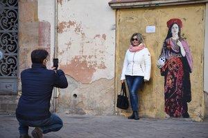 Unos viandantes se retratan al lado de la figura de Rosalía pintada por el artista TVBOY.