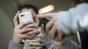 Jóvenes con móvil en un instituto de Barcelona.