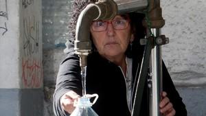 Una vecina de Vigo saca agua de una fuente pública.