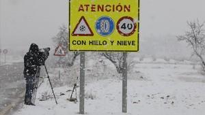 Un càmera de televisiógrava lestat duna carretera durantuna tempesta de neu.