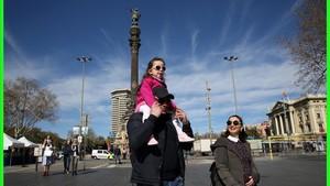 Una pareja, con su hija a hombros, pasea por las inmedicaciones del monumento a Colón, esta semana, en Barcelona.