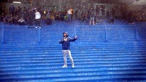 Un hincha de Boca canta bajo la intensa lluvia en la Bombonera.