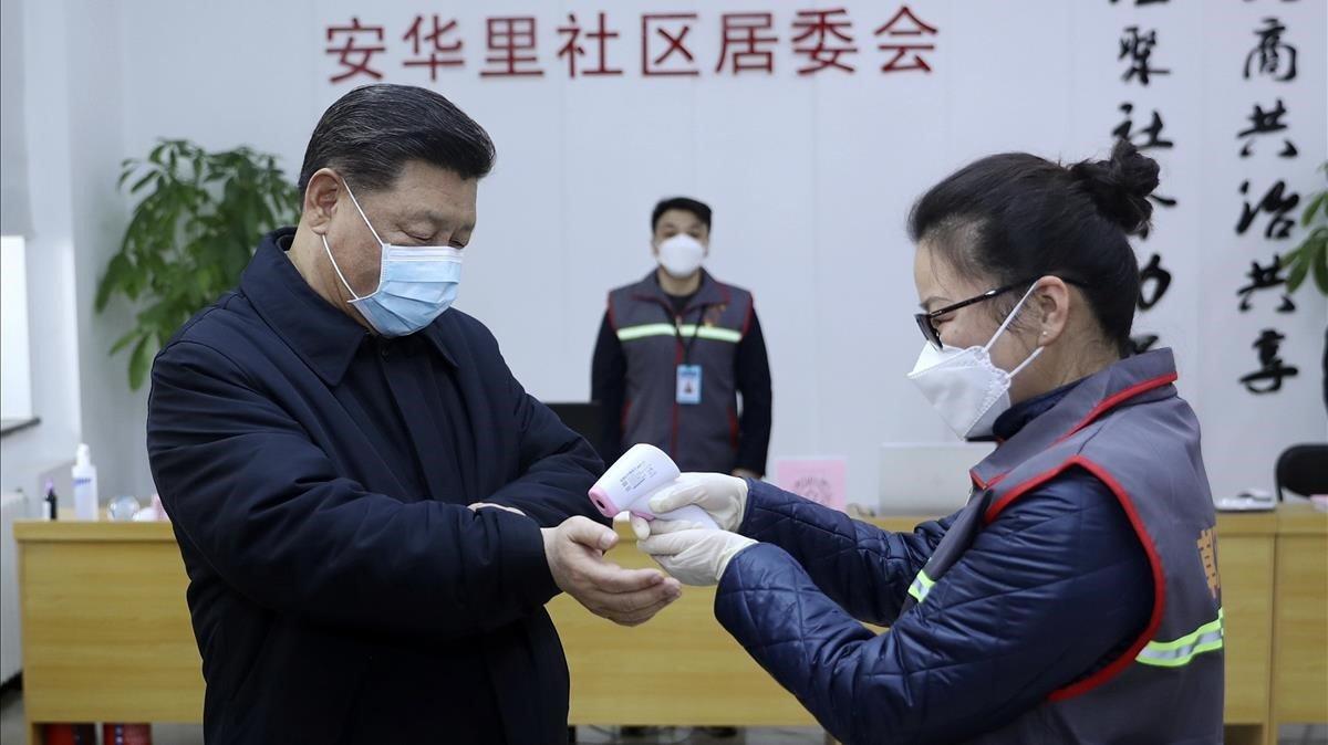 Una enfermera toma la temperatura al presidente chino Xi Jiping, ataviado con una mascarilla.