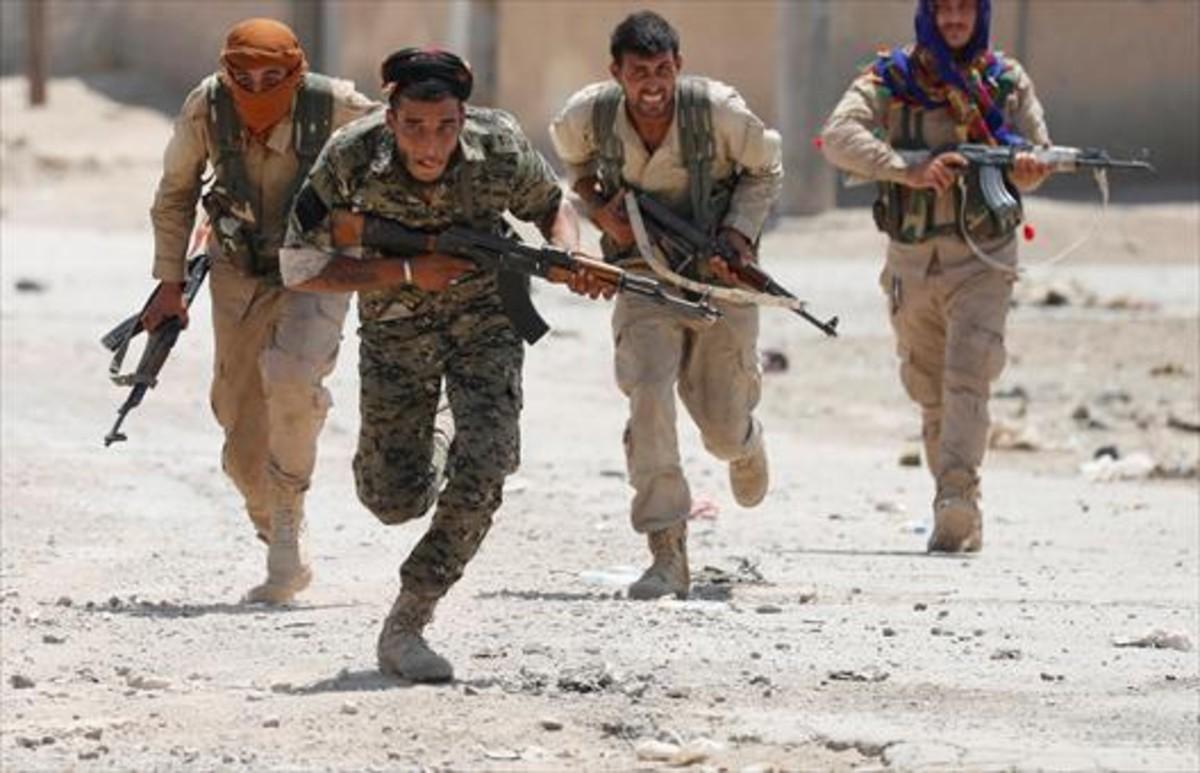 Milicianos kurdos en una calle de Raqqa.