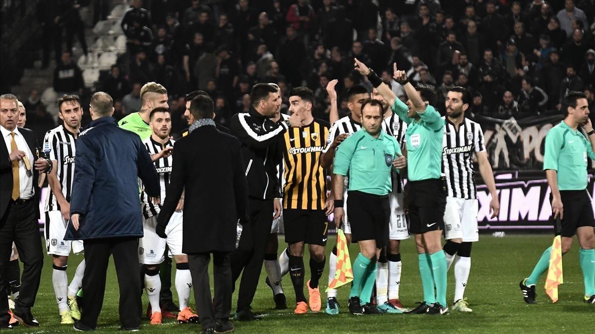 Árbitros y jugadores, durante los incidentes en el tramo final del partido en campo del PAOK.
