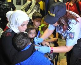 Una agente de policía checa escribe el número en la mano de un niño.