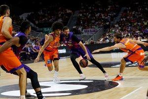 El barcelonista Mirotic (c) intenta culminar una jugada ante Valencia Basket.