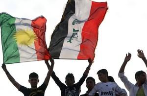 Aficionados de futbol sostienen banderas kurdas e iraquís en un partido de su selección. En una foto de archivo.