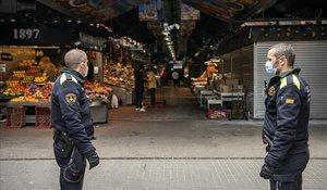 Agentes de la Guardia Urbana controlando el acceso a la Boqueria, con un 75% de puestos cerrados.
