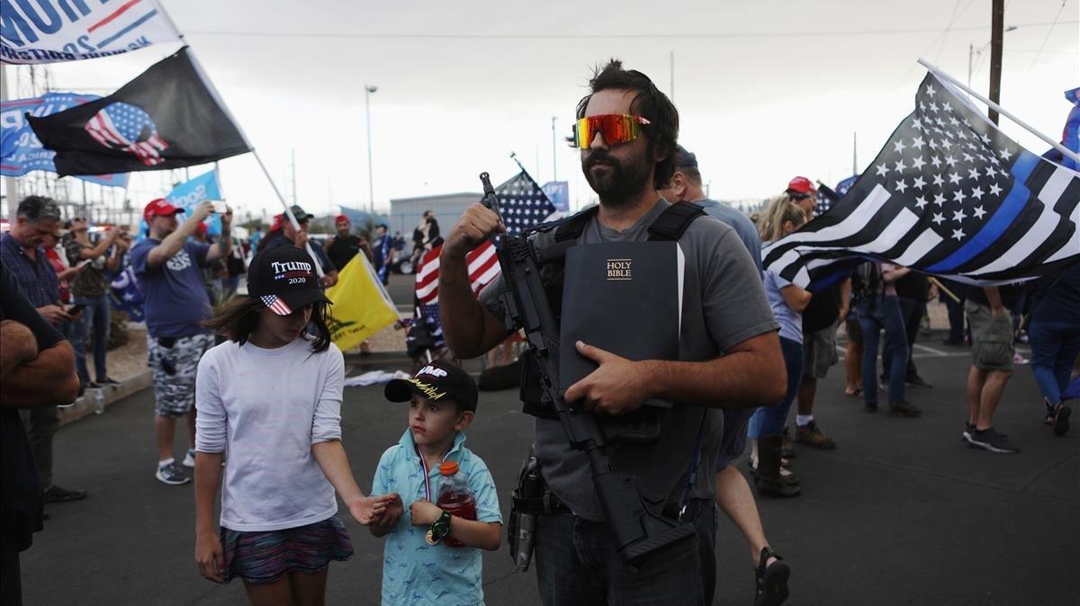 Un hombre armado que carga también con una Biblia ayer sábado en la protesta en el condado deMaricopa, en Arizona.