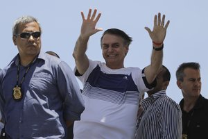 Brazil s President-elect Jair Bolsonaro waves at supporters as he arrives to watch an aerial performance by the private pilots  group a  Esquadrilha do Ceu  or a  Sky Squadron   at Barra beach in Rio de Janeiro  Brazil .  AP Photo Leo Correa