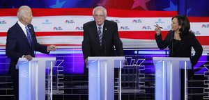 Former Vice President Joe Biden and Senator Kamala Harris debate racial issues as Senator Bernie Sanders listens during the second night of the first U S Democratic presidential candidates 2020 election debate in Miami Florida U S June 27 2019 REUTERS Mike Segar