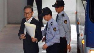Imagen de archivo delexpresidente surcoreano Lee Myung-bak mientras es escoltado por policías en lasala de un tribunal en Seúl.