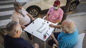 Cuatro hombres, ataviados con mascarillas, juegan una partida de dominó en la terraza de un bar de València, el pasado 27 de mayo.