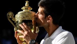 Djokovic besa el trofeo de campeón deWimbledon.
