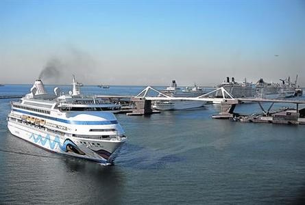 Un ferri humeante entra por la Bocana Nord junto al muelle Adossat repleto de grandes cruceros.
