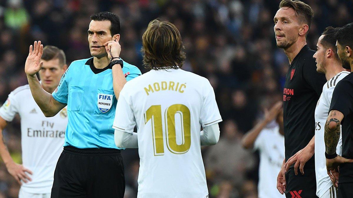 El árbitro Martínez Munuera escucha las indicaciones del VAR tras el gol de De Jong en la primera parte del Madrid-Sevilla.