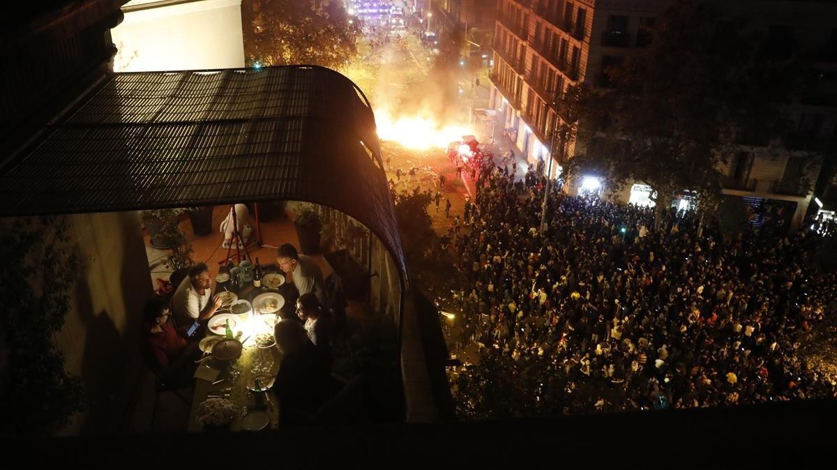 Un grupo cena en una terraza, mientras en la calle siguen los violentos altercados.