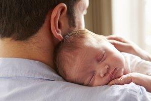 Un hombre abrazaa su hijo recién nacido.