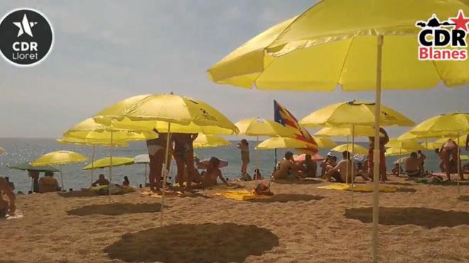 Els CDR col·loquen para-sols grocs a la platja de Blanes