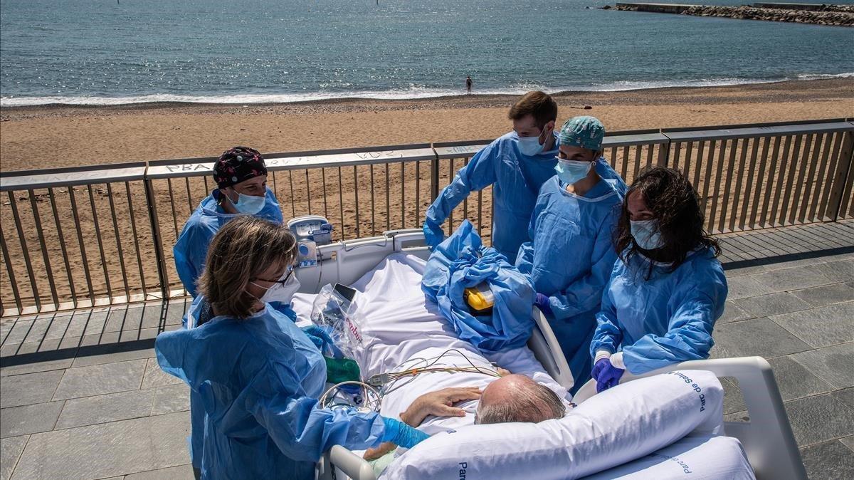 Isidre Correa, junto a su mujer y el equipo médico, frente a la playa delante del Hospital del Mar de Barcelona.