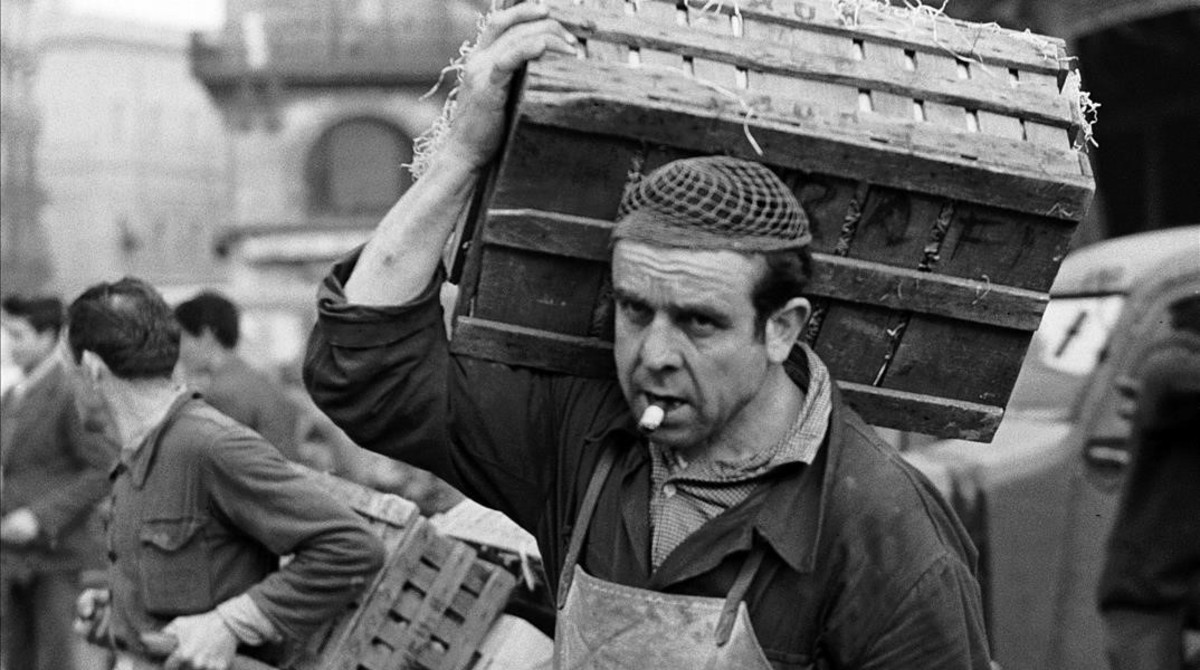 Un transportista de cajas de madera que contenían frutas y verduras en 1964.