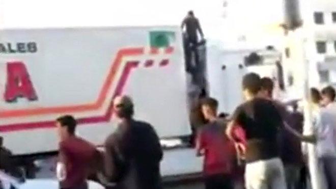 Menas tratan de abordar un camión en Nador, Marruecos.