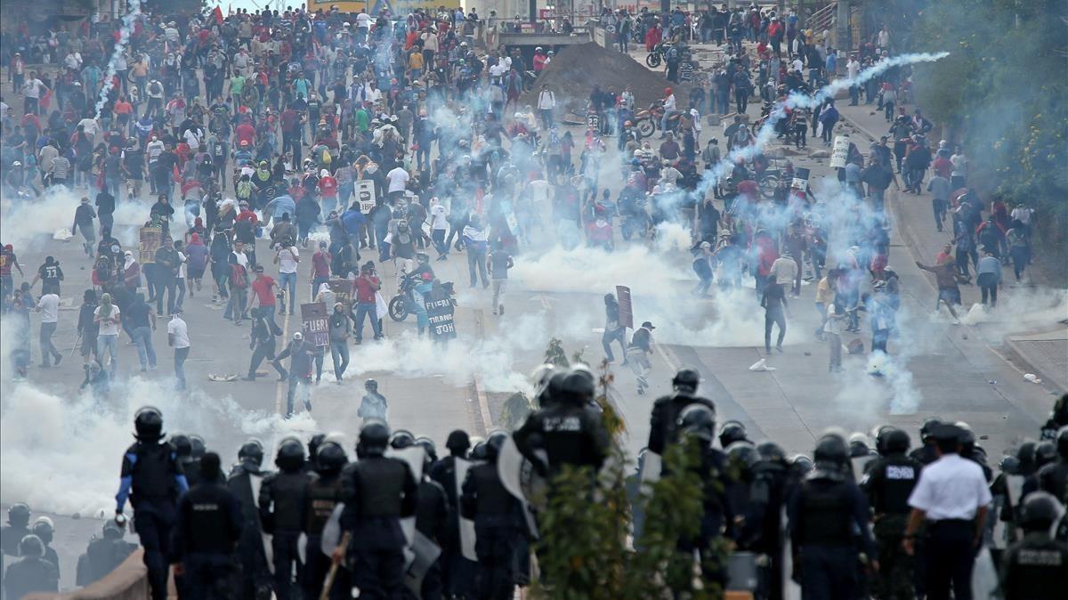 Opositores y policía se enfrentan cerca del Estadio Nacional de Tegucigalpa antes de la toma de posesión del presidente de Honduras, Juan Orlando Hernández.