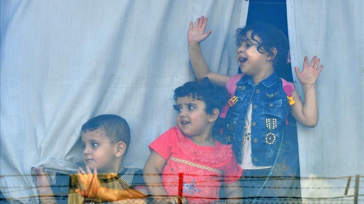 Niños refugiados sirios miran a través de la ventana de un autobús antes de abandonar Beirut este domingo de regreso a sus hogares en Siria.