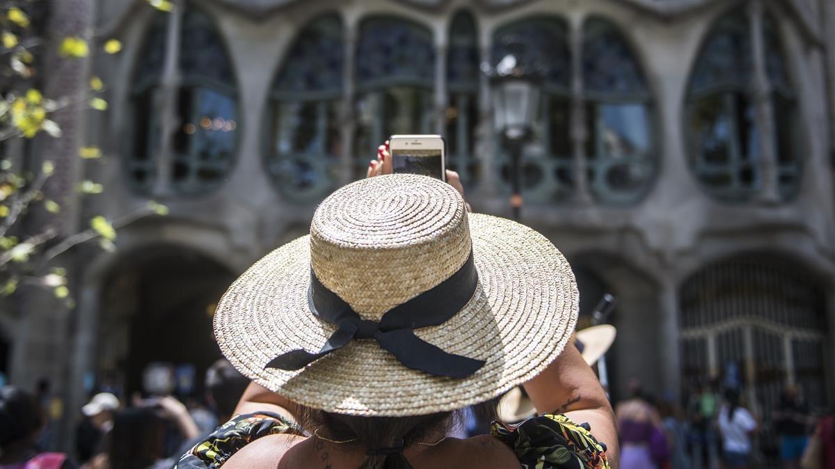 Turistas protegidos con sombreros frente a la casa Batlló.