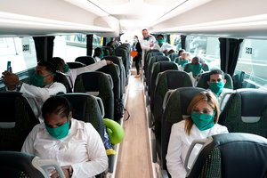 Some of the 39 Cuban doctors are seen inside a bus that will go to Andorra, at Madrid's Adolfo Suarez Barajas Airport, during the coronavirus disease (COVID-19) outbreak, Spain March 29, 2020. REUTERS/Juan Medina
