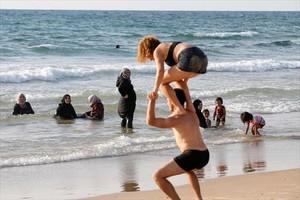 Varias mujeres se bañan vestidas y contemplan las acrobacias de una pareja en shorts y bañador en una playa de Tel Aviv.