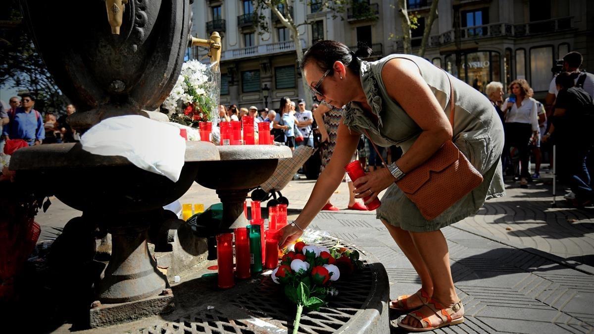 Una ciudadana deposita flores en la fuente de Canaletes. FERRAN NADEU