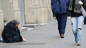 Una mujer pidiendo en el centro de Barcelona.