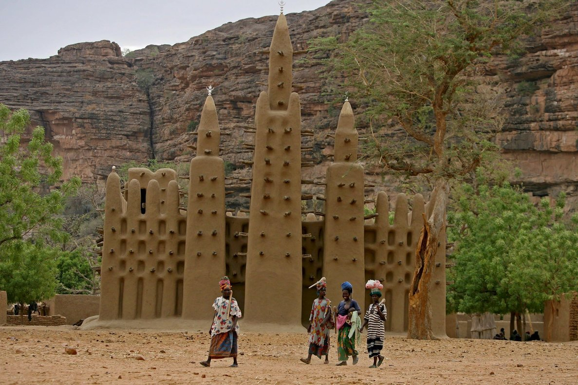 Varias mujeres pasan frente a una mezquita en una aldea dogon, en el centro de Mali.