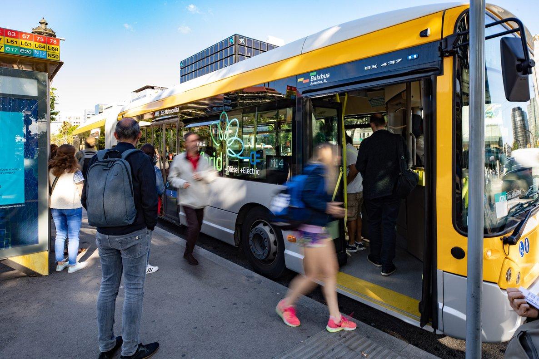 Viajeros a punto de subir en un autobús metropolitano híbrido de gestión indirecta