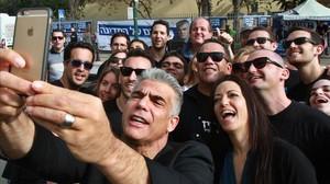 Yair Lapid, líder del partido de centroderecha Yesh Atid, se hace un selfi con su mujer y varios seguidores, tras votar este martes.