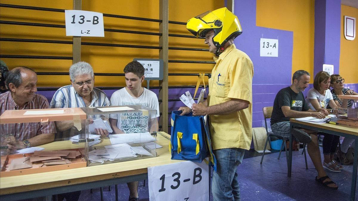Un empleado de Correos entrega los votos por correo en el colegio electoral de la escuela Santa Marta, en L'Hospitalet, en las elecciones generales del 2016.