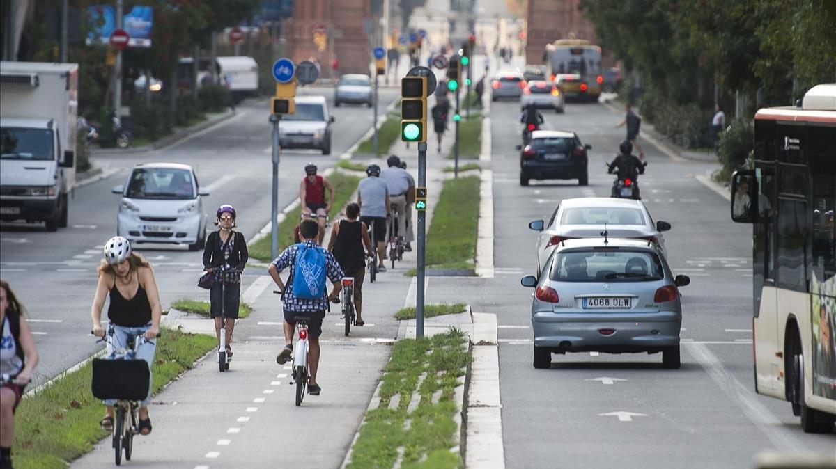 Patinetes, bicis, motos, coches, autobuses y peatones comparten espacio en el renovado paseo de Sant Joan.