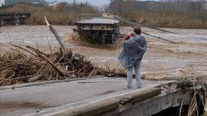 Un hombre toma una foto de un puente roto por la fuerza del agua del río Tordera.