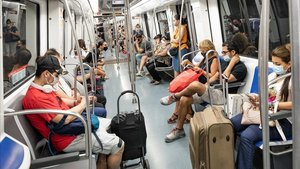 Pasajeros con mascarilla en la línea 5, este miércoles entre Diagonal y Sants.