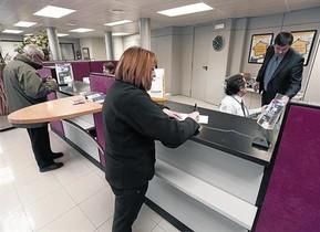 Una clienta realiza una gestión en una oficina bancaria en tona (Osona)