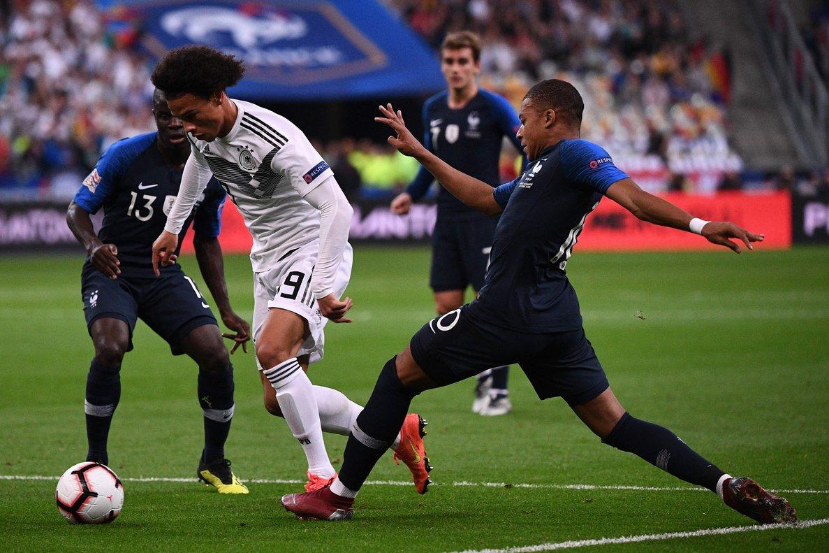 El alemán Leroy Sané (de blanco) regatea a jugadores de Francia.