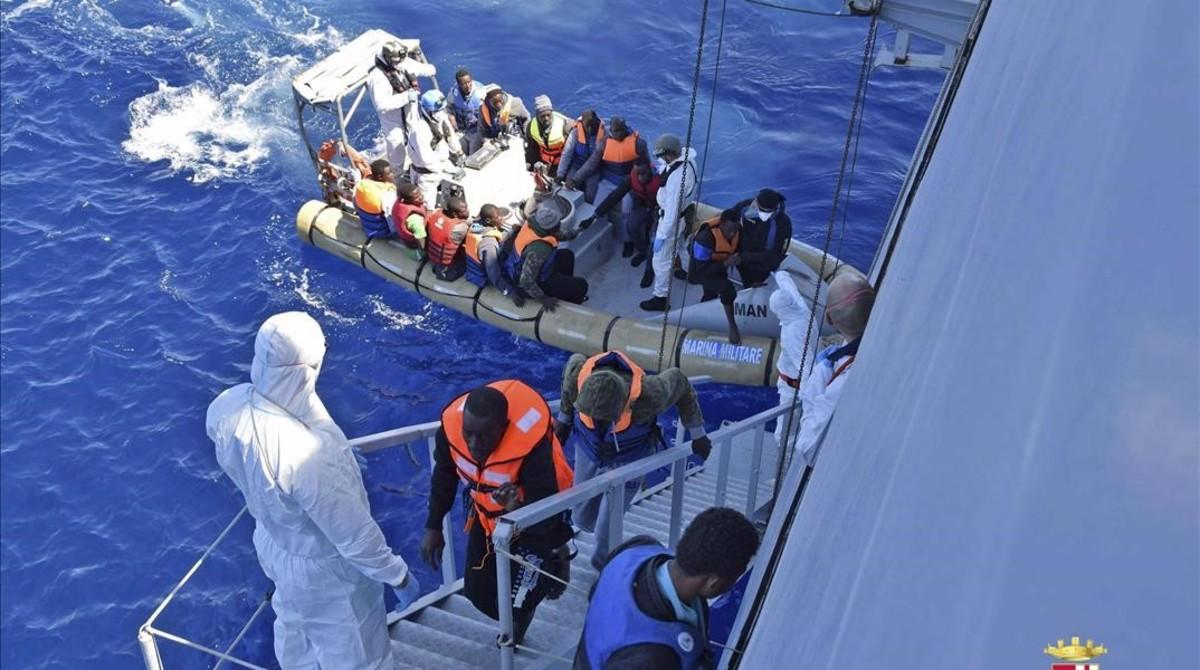 Un barco de la marina italiana rescata a un grupo de migrantes frente a las costas de Sicilia el lunes.
