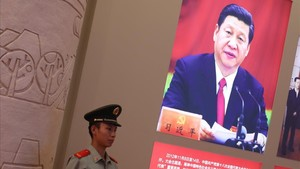 Un policía permanece junto a una foto del presidente chino, Xi Jinping, en Pekín.