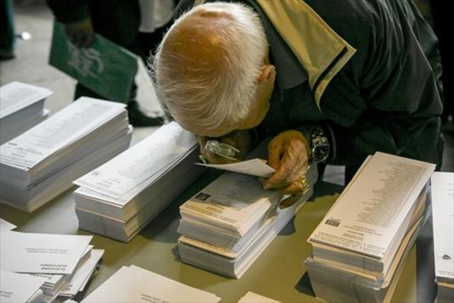 Un ciudadano examina con una lupa una papeleta electoral en Barcelona.