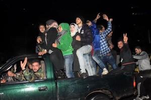 Un combatiente progubernamental carga a una mujer herida por un disparo rebelde cuando huía del barrio de Al Salhín, en Alepo.